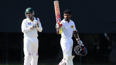 Sri Lankan cricketer Kaushal Silva (R) gestures after scoring a century (100 runs) as Pakistan wicketkeeper Sarfraz Ahmed looks on during the second day of the three-day warm-up match between Sri Lanka Board President's XI and Pakistan at the Colts Cricket Stadium in Colombo on June 12, 2015. AFP PHOTO/ Ishara S. KODIKARA        (Photo credit should read Ishara S.KODIKARA/AFP/Getty Images)