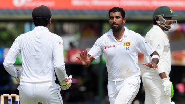 Sri Lanka's cricketer Dhammika Prasad (C) celebrates with wicketkeeper Dinesh Chandimal (L) the wicket of Pakistan cricketer Sarfraz Ahmed (R) during the fourth day of their second test match between Sri Lanka and Pakistan at the P. Sara Oval Cricket Stadium in Colombo on June 28, 2015. AFP PHOTO / LAKRUWAN WANNIARACHCHI        (Photo credit should read LAKRUWAN WANNIARACHCHI/AFP/Getty Images)