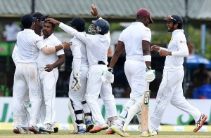 Sri Lankan cricketer Rangana Herath (2L) celebrates with teammates after dismissing West Indies Cricketer Darren Bravo (2R) during the final day of their second Test cricket match between Sri Lanka and the West Indies at the P. Sara Oval Cricket Stadium in Colombo on October 26, 2015. AFP PHOTO/ Ishara S. KODIKARA        (Photo credit should read Ishara S.KODIKARA/AFP/Getty Images)