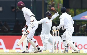 Sri Lankan cricket captain Angelo Mathews (C) takes a catch to dismiss West Indies Cricketer Marlon Samuels (L) during the final day of their second Test cricket match between Sri Lanka and the West Indies at the P. Sara Oval Cricket Stadium in Colombo on October 26, 2015. AFP PHOTO/ Ishara S. KODIKARA        (Photo credit should read Ishara S.KODIKARA/AFP/Getty Images)