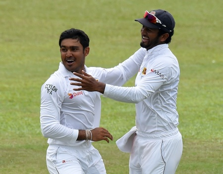 Sri Lankan cricketer Milinda Siriwardana (L) celebrates with teammate Dimuth Karunaratne (R) after dismissing West Indies cricketer Shai Hope during the final day of the second Test cricket match between Sri Lanka and the West Indies at the P. Sara Oval Cricket Stadium in Colombo on October 26, 2015. AFP PHOTO/ Ishara S. KODIKARA        (Photo credit should read Ishara S.KODIKARA/AFP/Getty Images)