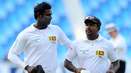 Sri Lankan bowler Rangana Herath (R) and Sri Lanka captain Angelo Mathews leave the pitch at the end of Pakistan's first innings during the opening day of the second Test match between Pakistan and Sri Lanka at the Dubai International Cricket Stadium in Dubai on January 8, 2014. AFP PHOTO/Ishara S. KODIKARA (Photo credit should read Ishara S.KODIKARA/AFP/Getty Images)