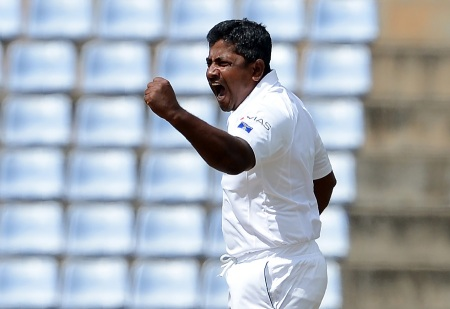 Sri Lanka's Rangana Herath celebrates with his teammates after he dismissed Australia's Usman Khawaja during the second day of their opening Test match between Sri Lanka and Australia at the Pallekele International Cricket Stadium in Pallekele on July 27, 2016. / AFP / LAKRUWAN WANNIARACHCHI        (Photo credit should read LAKRUWAN WANNIARACHCHI/AFP/Getty Images)