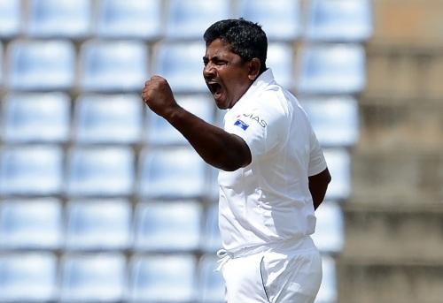 Sri Lanka's Rangana Herath celebrates with his teammates after he dismissed Australia's Usman Khawaja during the second day of their opening Test match between Sri Lanka and Australia at the Pallekele International Cricket Stadium in Pallekele on July 27, 2016. / AFP / LAKRUWAN WANNIARACHCHI        (Photo credit should read LAKRUWAN WANNIARACHCHI/AFP/Getty Images)