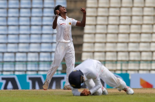 Sri Lanka's bowler Lakshan Sandakan celebrates as Kusal Mendis, foreground takes a catch to dismiss Australia's Steve O' Keefe during day two of the first test cricket match between Sri Lanka and Australia in Pallekele, Sri Lanka, Wednesday, July 27, 2016. (AP Photo/Eranga Jayawardena)